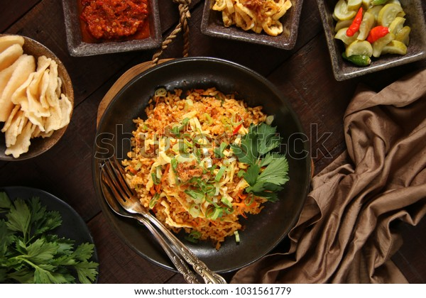 Nasi Goreng Jawa. The popular Indonesian rice dish of fried rice; cooked Javanese style with sweet soy sauce. Accompanied with condiments of chili sauce, pickled cucumber, crackers, and omelet.