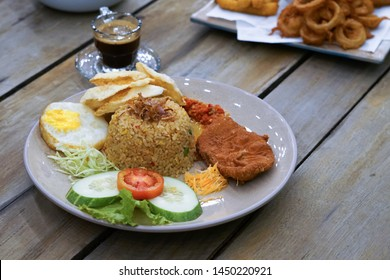Nasi Goreng Kampung. fried rice with chicken katsu and vegetable. Wood Background