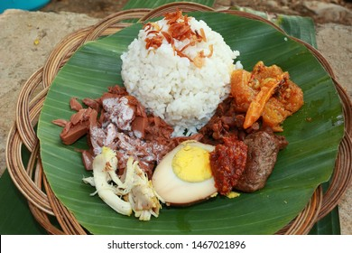 Nasi Gudeg. A signature rice dish from Jogjakarta. Jack fruit stew accompanied with spicy stew of cattle skin crackers and white chicken curry. In the background are the individual dish of gudeg mea