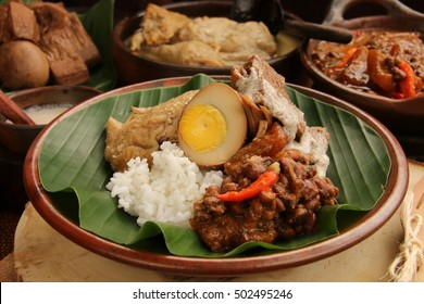 Nasi Gudeg. A signature rice dish from Jogjakarta. Jack fruit stew accompanied with spicy stew of cattle skin crackers and white chicken curry. In the background are the individual dish of gudeg meal.