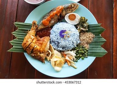 Nasi Kerabu ist ein malaiisches Reisgericht, eine Art Nasi-Ulam, in dem blauer Reis mit getrocknetem Fisch, frittiertem Huhn, Cracker, gesalzenem Ei, Beizen und anderen Salaten gegessen wird.
