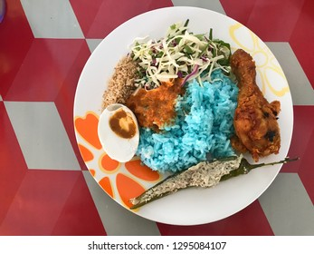 Nasi kerabu traditional food in Malaysia on the dining table. Its blue color. Use coconut which has been fried and mixed with rice. a combination of vegetables, duck eggs and side dishes