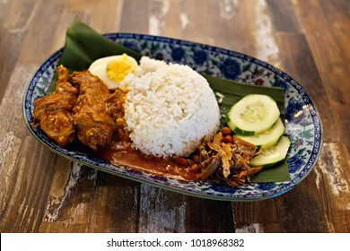 Nasi Lemak Chicken Rendang-Malaysian cuisine. A fragrant rice dish cooked in coconut milk and pandan leaf commonly found in Malaysia. Served with sambal, anchovies, peanut egg and cucumber.