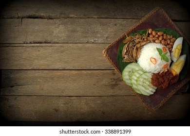 Nasi Lemak , famous Malaysian cuisine served on wooden table. top view
