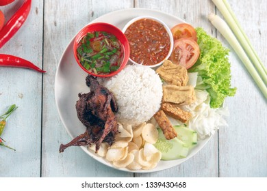 Nasi lemak kukus with quail meat, popular traditional Malaysian local food. Flat lay top down overhead view.