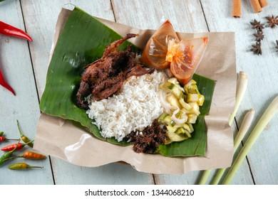 Nasi lemak kukus with quail, popular traditional Malay local food. Flat lay top down overhead view.