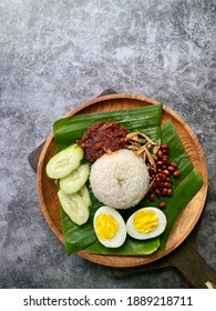 Nasi lemak (Malay fragrant rice dish cooked in coconut milk and pandan leaf) with recipe ingredients on wooden plate. Ready to eat for breakfast