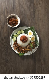 Nasi Lemak. Malay fragrant rice dish cooked in coconut milk and pandan leaf. Overhead view on rustic wooden background.