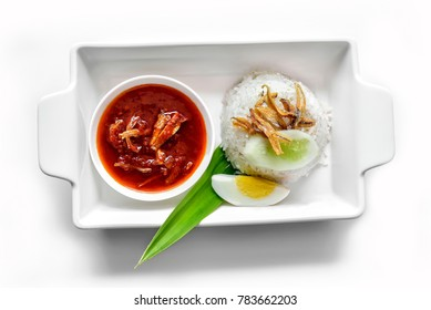 Nasi lemak, a Malay fragrant rice dish cooked in coconut milk and pandan leaf, completed with boiled egg, fried anchovy, cucumber slices and sambal or chili gravy.