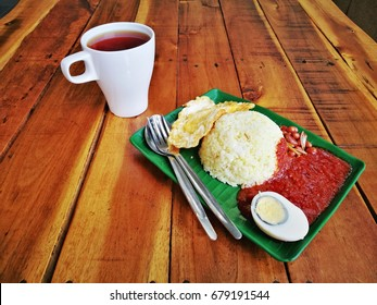 Nasi lemak in Malaysia. Known as fragrant rice cooked with coconut milk and enriched with chili paste, cucumber and smell of pandan leaves. Served with egg and plain a cup of tea.
