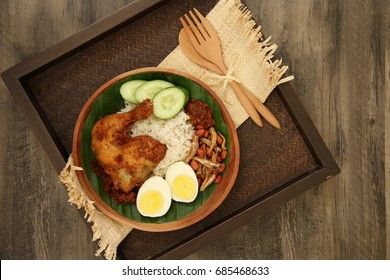 Nasi Lemak. Malaysian fragrant rice dish, served with fried chicken, egg, peanuts, anchovies, and chili paste. Served on a wooden plate and arranged on a woven tray with wooden cutlery set aside.