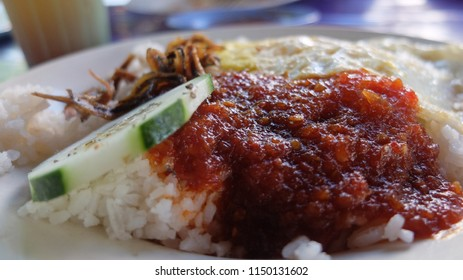Nasi Lemak; Popular Malaysian breakfast consists of Rice cooked in Coconut cream served with specially made Chilly sauce, friend anchovies, boiled egg and raw cucumber.