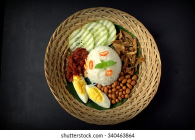 Nasi Lemak-Malaysian cuisine. A fragrant rice dish cooked in coconut milk and pandan leaf commonly found in Malaysia. Served with sambal, anchovies, peanut and cucumber.