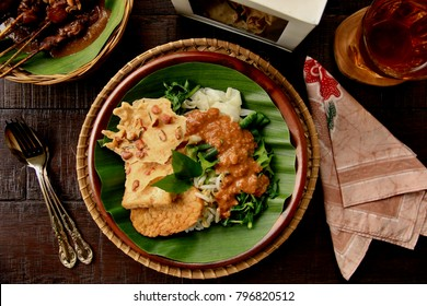 Nasi Pecel. Traditional Javanese rice dish of steamed rice with vegetable salad, peanut dressing, tempeh, beancurd and crackers.