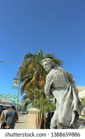 Nassau, Bahamas Dec. 12, 2018 – Visitors walk by Edwin Russell statue of Governor Woodes Rogers at British Colonial Hotel. In 1718 Rogers publicly hung pirates to help restore seafaring commerce.