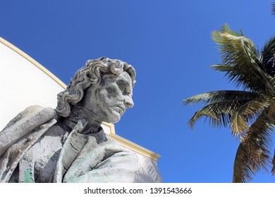 Nassau, Bahamas Dec. 12, 2018 – Edwin Russell statue of Governor Woodes Rogers at British Colonial Hotel. In 1718 Rogers publicly hung pirates to help restore seafaring commerce. Palm trees visible.