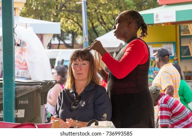 NASSAU, BAHAMAS, December 11, 2015: Female tourist having her hair braided by a Bahamian woman in downtown Nassau, Bahamas
