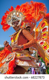 NASSAU, THE BAHAMAS - JANUARY 1 - Female troop leader dressed in bright orange feathers, dances in Junkanoo, a traditional island cultural festival on Jan 1, 2011 in Nassau