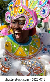 NASSAU, THE BAHAMAS - JANUARY 1 - Smiling female dancer dressed in hugh pink headress, dances in Junkanoo, a traditional island cultural festival in Nassau, Jan 1, 2011