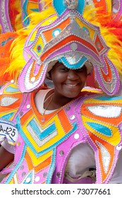 NASSAU, THE BAHAMAS - JANUARY 1 - Smiling, dancing woman in pink and orange costume, performs in Junkanoo, a traditional island cultural festival in Nassau, Jan 1, 2011