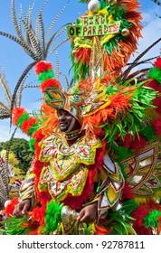 NASSAU, THE BAHAMAS - JANUARY 1 : Smiling male performer dressed in a huge orange and green headdress, dances in Junkanoo, a traditional island cultural festival in Nassau, Jan 1, 2011