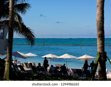 Nassau, Bahamas - March 1, 2018:  Tourists relaxing on a beach on the Caribbean Sea in Nassau, Bahamas
