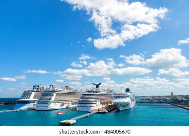 Nassau, Bahamas-February 18, 2016: Large luxury cruise ships of Carnival, Norwegian and Royal Caribbean cruise lines docked in port of Nassau, Bahamas on sea water and cloudy sky background