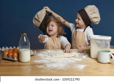 Nasty schoolboy in chef uniform teasing his crying little sister, taking off her cap while making dough together in kitchen, standing at counter with dough, milk, flour and eggs, baking cookies