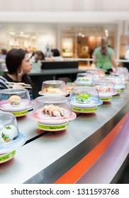 Natick, MA, USA - Oct 7, 2012: Sushi moving at conveyor belt sushi restaurant