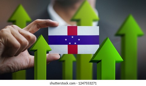 Nation Growth Concept, Green Up Arrows - Businessman Holding Card of Netherlands Antilles Flag