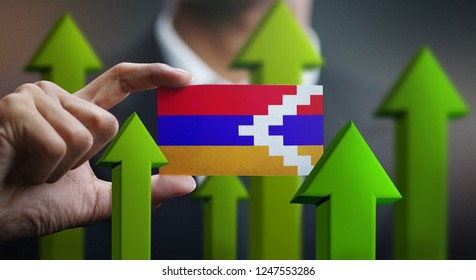 Nation Growth Concept, Green Up Arrows - Businessman Holding Card of Nagorno-Karabakh Republic Flag