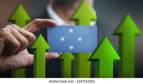 Nation Growth Concept, Green Up Arrows - Businessman Holding Card of Federated States of Micronesia Flag