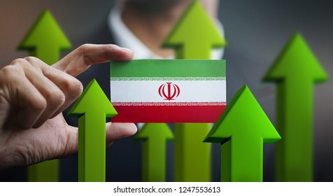 Nation Growth Concept, Green Up Arrows - Businessman Holding Card of Iran Flag