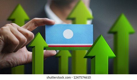 Nation Growth Concept, Green Up Arrows - Businessman Holding Card of Sakha Republic Flag