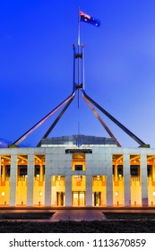 National Australian flag on flagpole on top of public government building - parliament house in Canberra on capitol hill at sunset with bright illumination.