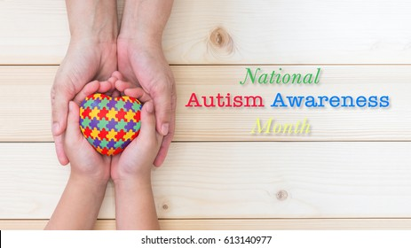 National Autism Awareness month in April with heart in puzzle jigsaw pattern on autistic kid palms supported by family caregiver hands