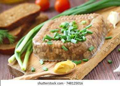 National cuisine. Russian traditional dish - Holodets. Homemade jellied meat with garlic and spices garnished with mustard and spring onion. The best food for Russian vodka.