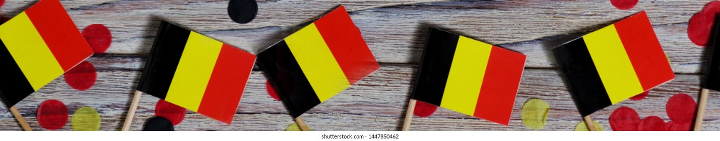 national day of Belgium , July 21. national Belgian festival. the concept of celebration, fun, patriotism and freedom. mini flags and confetti on white wooden background. banner
