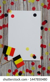 national day of Belgium , July 21. national Belgian festival. the concept of celebration, fun, patriotism and freedom. mini flags and confetti with sheets of white paper on white wooden background