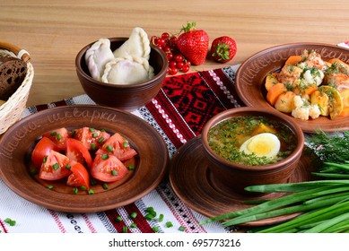 National dinner of Ukraine: vegetable soup with boiled egg, salad with tomatoes in sunflower oil, vareniki with berries, vegetable ragout with tablecloth on a wooden table.