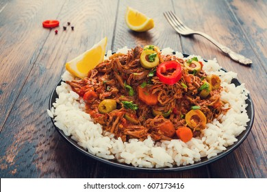 The national dish of Cuba, Ropa Vieja, tender shredded beef stewed with vegetables and spices on a black plate with a boiled rice on the wooden table.