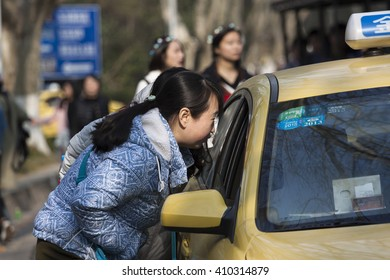NATIONAL DR.SUN YAT-SAN MEMORIAL HALL,NANJING,JIANGSU PROVINCE,CHINA-MAY 05: Unidentified a women commune with taxi driver go to somewhere on May 05,2016 in Nanjing city,Jiangsu province,China.