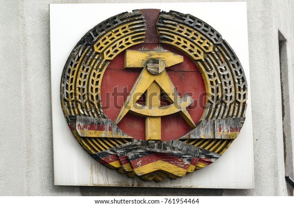 The national emblem of the German democratic Republic (GDR),with partial loss of the paint, miraculously preserved on the wall of a building near checkpoint Charlie, Berlin, Germany