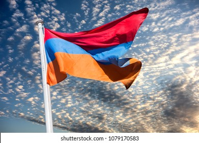 The national flag of Armenia, the Armenian Tricolour, flutters against the background of thunderclouds and a strong wind.