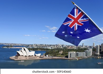 The National flag of Australia flies above Sydney Harbor.