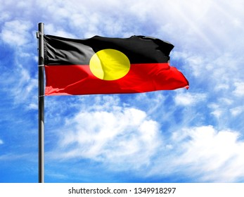 National flag of Australian Aboriginal on a flagpole in front of blue sky.