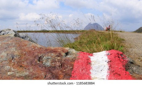 The national flag of Austria on a stone with at the background a lake and mountains (Typical Austria Alps Landscape)