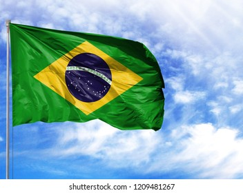 National flag of Brazil on a flagpole in front of blue sky