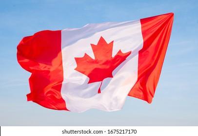 National Flag of Canada. Canadian flag on blue sky background.