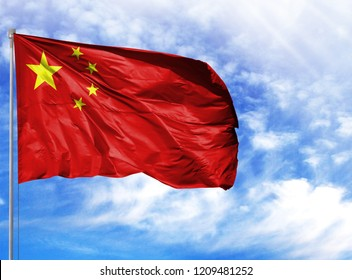 National flag of China on a flagpole in front of blue sky